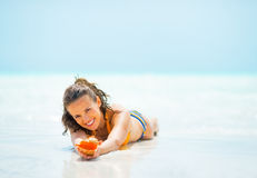 Young woman with shell laying on sea shore Stock Photos