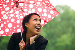 Young Woman Sheltering From Rain Under Umbrella Royalty Free Stock Photography