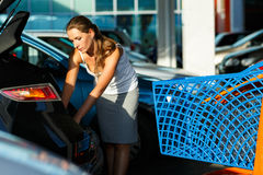 Young woman shifts the purchase from shopping cart in the trunk Royalty Free Stock Image