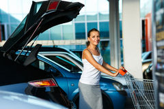 Young woman shifts the purchase from shopping cart in the trunk Stock Image