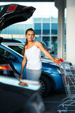 Young woman shifts the purchase from shopping cart in the trunk Royalty Free Stock Photography