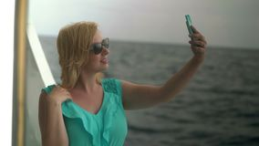 Young woman on ship desk taking selfie stock video
