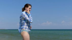 A young woman in a shirt and bikini stands in the sea