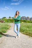 Young woman in shirt and jeans standing on path at park Stock Photography