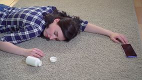Young woman lies unconscious at home on the floor after a seizure before reaching for a smartphone. Young woman in a shirt lies unconscious at home on the floor stock video footage