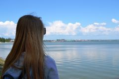 A young woman in a shirt, looking at the sea . Rear view close-up stock photography