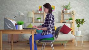 Young woman sits on a round orthopedic pillow and starts working on a laptop