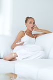 Young woman is in shock while watching tv Royalty Free Stock Image