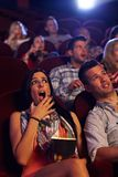 Young woman shocked at cinema. Young women watching horror movie at cinema, looking shocked, holding popcorn in hand stock photos