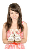 Young woman with shoes. The young woman holds female shoes in hands, is pleased, on the white background, isolated Royalty Free Stock Photo