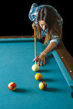 Young woman shooting pool. Twenty something girl about to shoot a combination Royalty Free Stock Photo