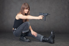 Young woman shoots from pistol sitting on one leg Stock Photos