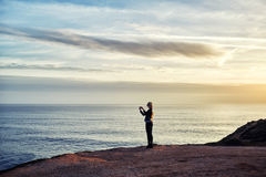 Young woman shoots video of an amazing scenery view of calm ocean on cell telephone Stock Photos