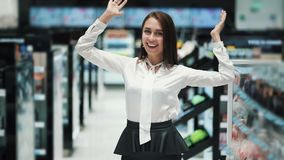 Young woman shop assistant shows emotion, laughs, funny video, slow motion. Beautiful girl in mall stock video footage
