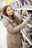 Young woman in shop choosing and buying pantyhose Stock Photos
