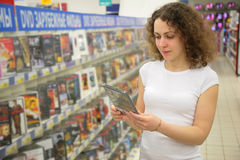 Young woman in shop holds in hands dvd stock images