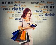 Young woman shopaholic carrying bags holding a empty wallet, shocked about huge debt amount, has no money for shopping in her. Pouch. Overspending concept royalty free stock images