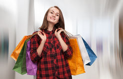 Young woman with shoping bags. On blurred background of a trading hall stock photography