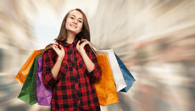 Young woman with shoping bags. Sale. Happy young woman with shoping bags on blurred city street background royalty free stock images