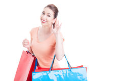 Young woman shopper making cannot hear you gesture. Concept and smiling isolated on white background with copy text space Royalty Free Stock Image
