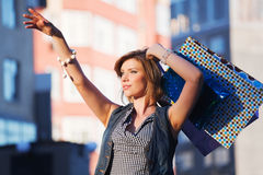 Happy young fashion woman with shopping bags on city street Stock Photography
