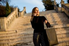 Young woman with shopping bag and mobile phone outdoor. Portrait of young woman with shopping bag and mobile phone outdoor Stock Photos