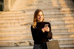 Young woman with shopping bag and mobile phone outdoor. Portrait of young woman with shopping bag and mobile phone outdoor Royalty Free Stock Photo