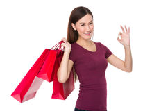 Young woman with shopping bag and ok gesture Stock Image