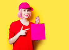 Young woman with shopping bag. Portrait of beautiful smiling young woman with shopping bag on the wonderful yellow studio background Stock Photography