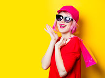 Young woman with shopping bag. Portrait of beautiful smiling young woman with shopping bag on the wonderful yellow studio background Royalty Free Stock Image