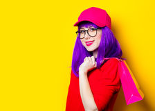 Young woman with shopping bag. Portrait of beautiful smiling young woman with shopping bag on the wonderful yellow studio background Stock Photos