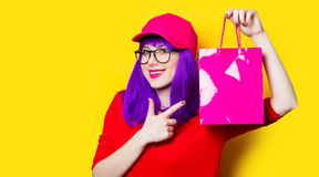 Young woman with shopping bag. Portrait of beautiful smiling young woman with shopping bag on the wonderful yellow studio background Stock Image