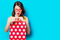 Young woman with shopping bag. Portrait of beautiful surprised young woman with shopping bag on the wonderful blue studio background Royalty Free Stock Photos
