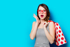 Young woman with shopping bag. Portrait of beautiful surprised young woman with shopping bag on the wonderful blue studio background Stock Image