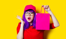 Young woman with shopping bag. Portrait of beautiful surprised young woman with shopping bag on the wonderful yellow studio background Stock Photography