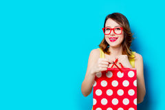 Young woman with shopping bag. Portrait of beautiful young woman with shopping bag on the wonderful blue studio background Royalty Free Stock Image