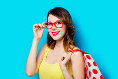 Young woman with shopping bag. Portrait of beautiful young woman with shopping bag on the wonderful blue studio background Stock Image