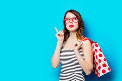 Young woman with shopping bag. Portrait of beautiful young woman with shopping bag on the wonderful blue studio background Stock Photo