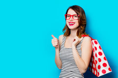 Young woman with shopping bag. Portrait of beautiful young woman with shopping bag on the wonderful blue studio background Royalty Free Stock Photo