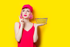 Young woman with shopping bag. Portrait of beautiful young woman with shopping bag on the wonderful yellow studio background Royalty Free Stock Images