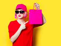 Young woman with shopping bag. Portrait of beautiful young woman with shopping bag on the wonderful yellow studio background Royalty Free Stock Photos