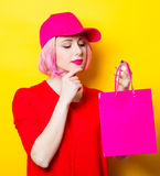 Young woman with shopping bag. Portrait of beautiful young woman with shopping bag on the wonderful yellow studio background Stock Photo