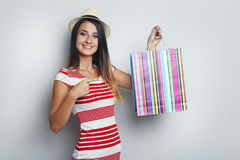 Young woman with shopping bag. Portrait of young woman with shopping bag on grey background Royalty Free Stock Photography