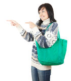 Young woman with shopping bag showing something Stock Images