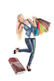 Young woman with shopping bags. Attractive young woman talking on cell phone and losing her shopping bag Royalty Free Stock Photos