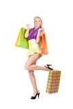 Young woman with shopping bags. Happy young woman with shopping bag on heel over white background Royalty Free Stock Photos