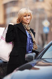Young woman with shopping bags at the car Royalty Free Stock Image