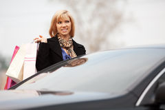 Young woman with shopping bags at the car Royalty Free Stock Images