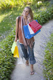 Young Woman with Shopping Bags and Cell Phone Stock Photography