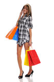 Young woman with shopping bags and cell phone Royalty Free Stock Image